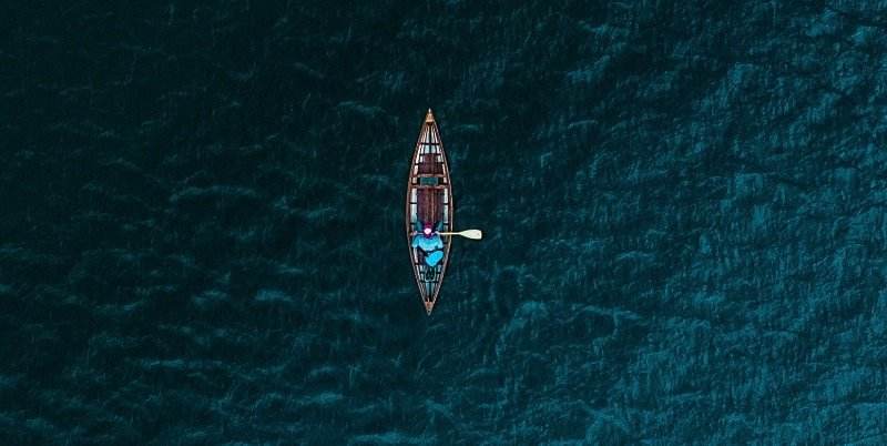 a man on a boat in the middle of nowhere